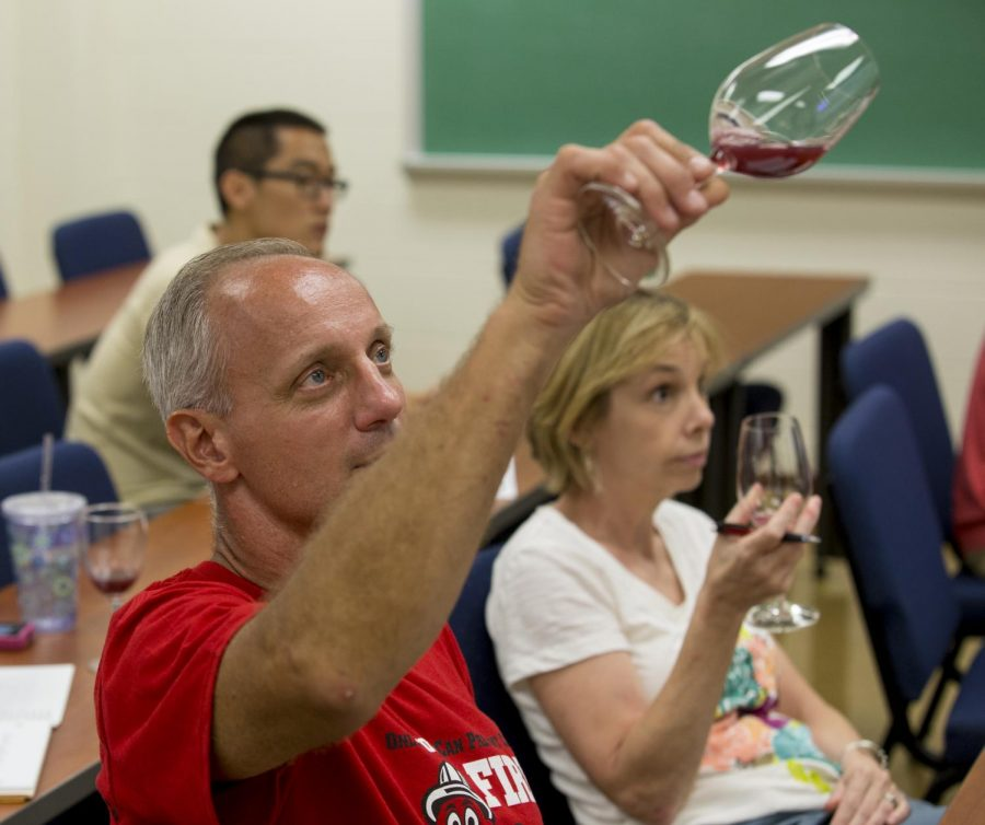 Bob Austin checks the color of unfermented grape juice grown in Western's vineyards during the Wine Fundamentals class Sept. 10, 2013, in the Environmental Sciences and Technology building at Western Kentucky University. Austin says he is taking the class because he finds the history of wine interesting.