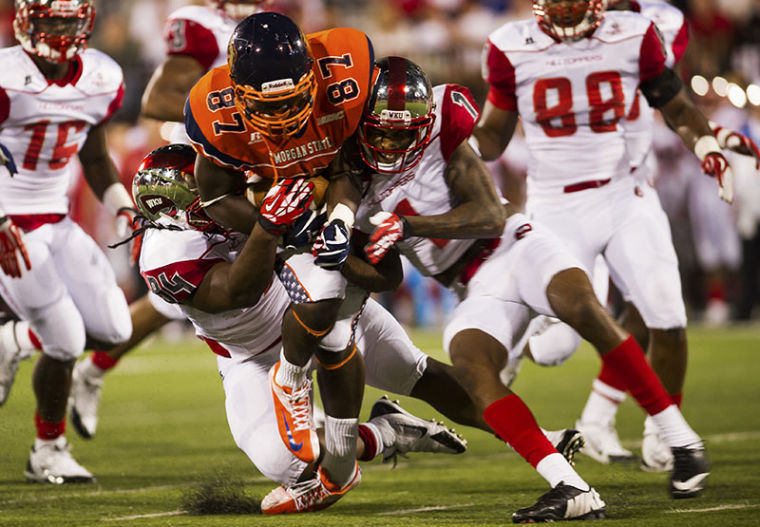 WKU's Bryan Shorter, left, and DeVante Thomas, right, tackle Morgan State's Nate Ingram during their game at Western Kentucky University on Saturday, September 21, 2013. Western would go on to win 58-17.
