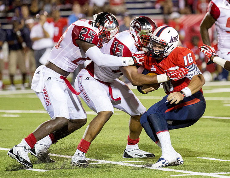 Senior Chuck Franks (25), left, and senior Xavius Boyd (13) tackle South Alabama's Montell Garner (16) during the first half of WKUÕs game against South Alabama on Sept. 14 at Ladd-Peebles Stadium in Mobile, Ala.