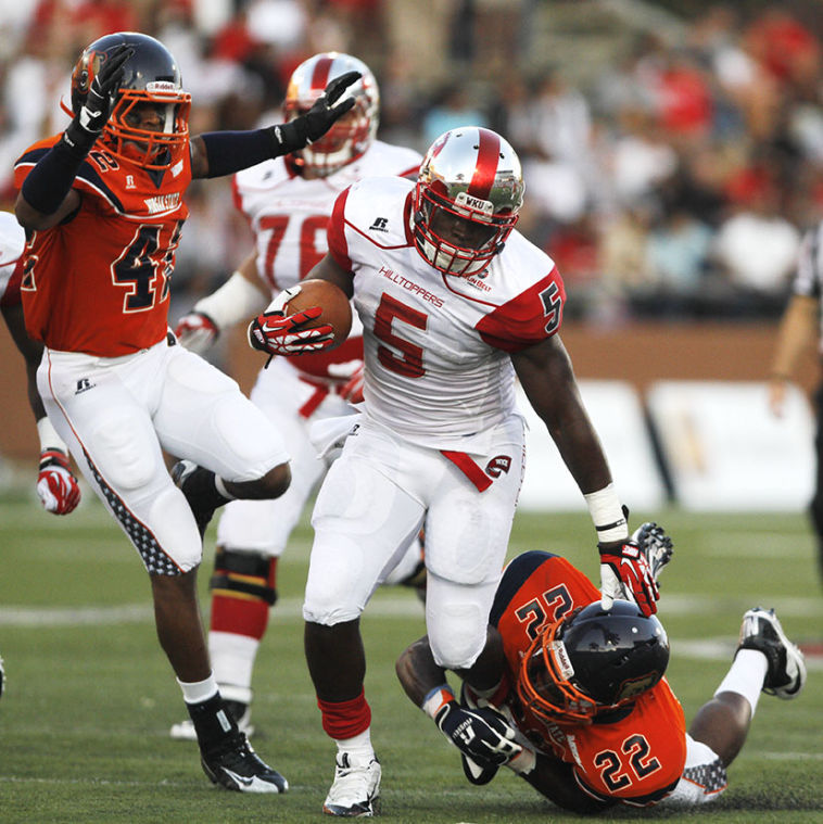 Morgan State junior defensive back Nathan Ayers tries to pull WKU senior running back Antonio Andrews to the ground after Andrews received a handoff from sophomore quarterback Nelson Fishback.