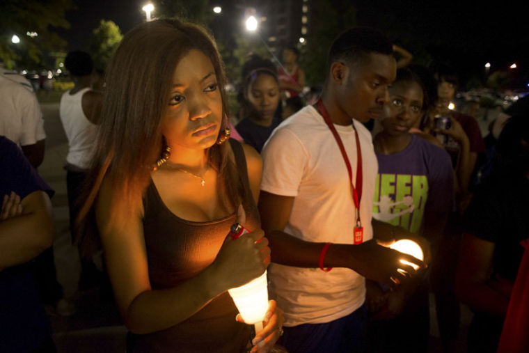 Sophomore DeVari Dudley, 20, listens as WKU students tell stories at a candlelight vigil for Larry Thomas outside of Pearce Ford Tower.