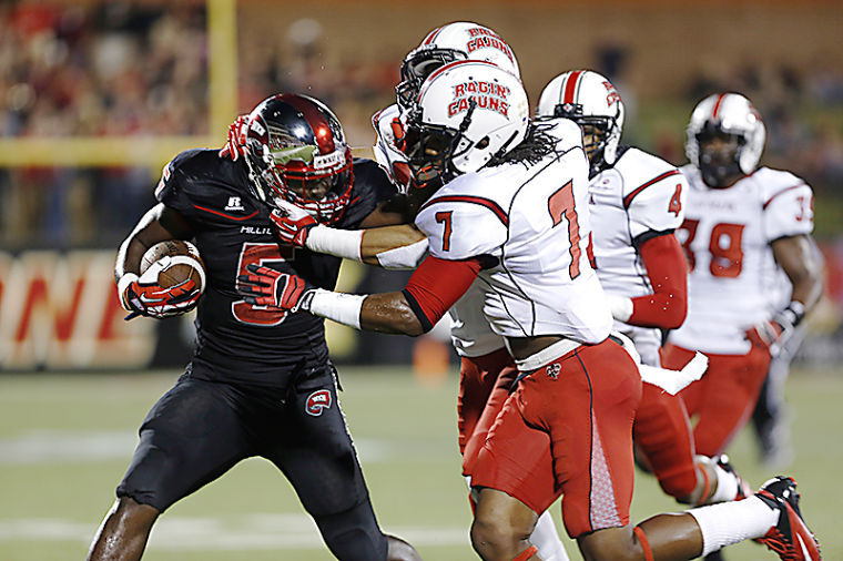 WKU's Running Back Antonio Andrews stiff arms Louisiana's defense during their game against Louisiana at Western Kentucky University on Tuesday, October 15, 2013.
