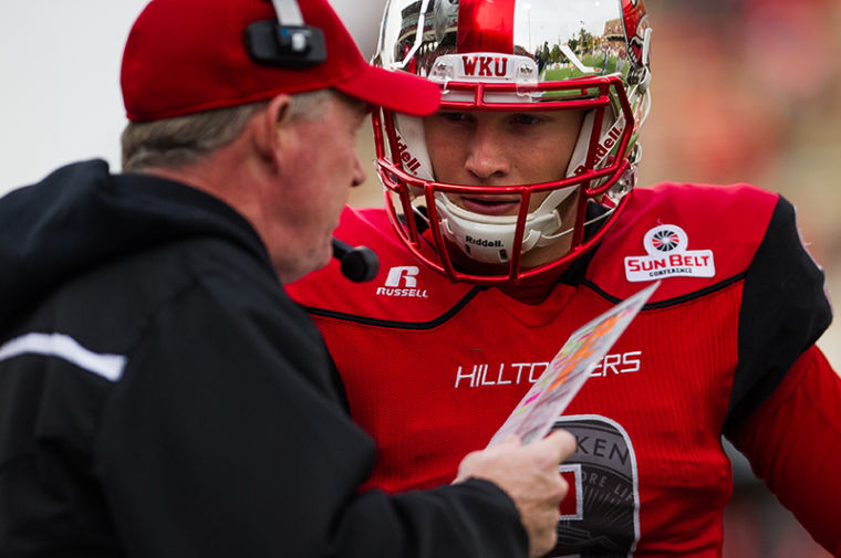 Western Kentucky University's Nelson Fishback talks to coach Bobby Petrino during their game at against Troy at WKU on Saturday, October 26, 2013.