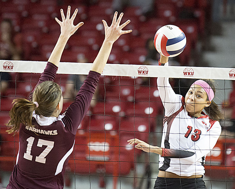 Middle hitter Noelle Langenkamp (13) spikes the ball past middle blocker Alannah Cullum (17) during WKU's 3-1 victory over the University of Louisiana Monroe Friday, Oct. 11, 2013, at E. A. Diddle Arena in Bowling Green, Ky.