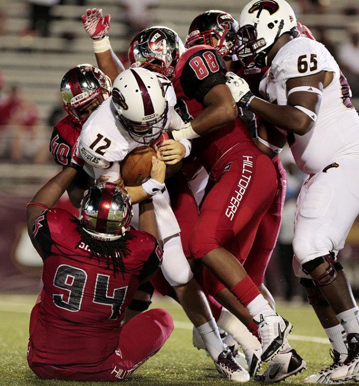 WKU+sophomore+defensive+lineman+Bryan+Shorter%2894%29%2C+sophomore+defensive+lineman+Gavin+Rocker+%2888%29%2C+and+senior+linebacker+Bar%27ee+Boyd+wrap+up+Louisiana-Monroe+sophomore+quarterback+Brayle+Brownduring+the+second+half+of+their+game+at+Malone+Stadium+in+Monroe%2C+Louisiana.+The+defensive+shut-out+ULM+in+the+second+half.