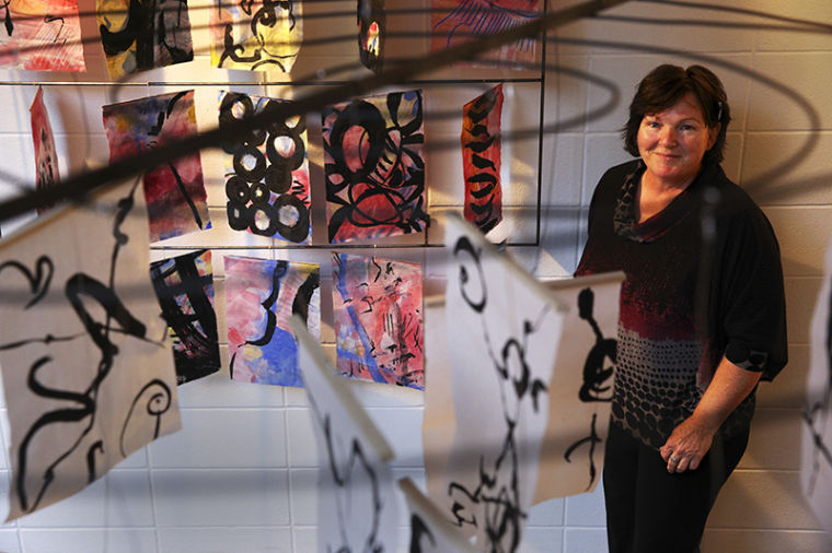 WKU alumna Lynne Ferguson stands among her art exhibit, which includes paintings on rice paper. The exhibit will have an opening reception Friday at 5 p.m. and remain open until Dec. 15 in the Kentucky Museum.