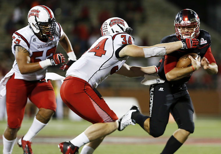 WKU%27s+quarterback+Nelson+Fishback+tries+to+avoid+being+tackled+during+their+game+against+Louisiana+at+Western+Kentucky+University+on+Tuesday%2C+October+15%2C+2013.%C2%A0