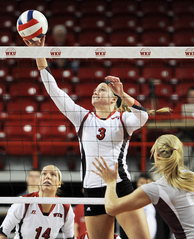 Junior middle hitter Heather Boyan sets a ball over the net her team's game against University Arkansas Little Rock. The Lady Toppers won the match 3-0.
