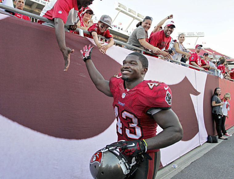 Tampa Bay Buccaneers running back Bobby Rainey (43) gives fans high five as he leaves the field following a 41-28 win over the Atlanta Falcons at Raymond James Stadium on Sunday, November 17, 2013.