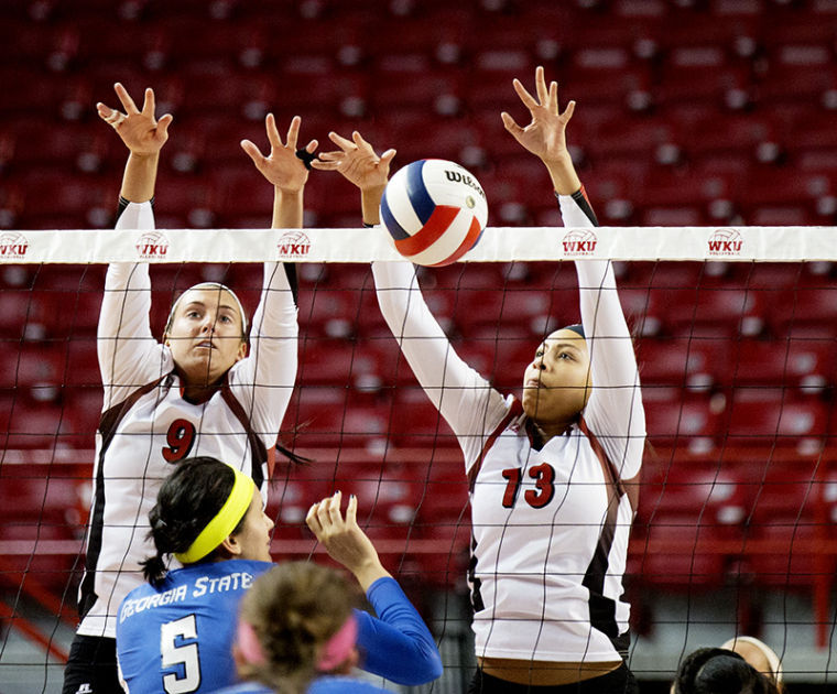 Middle hitter Noelle Langenkamp (13) blocks a spike by middle blocker Andrea Book (5) as outside hitter Paige Wessel (9) assists during WKUs 3-0 victory over Georgia State Wednesday, Nov. 13, 2013, at E.A. Diddle Arena in Bowling Green, Ky.