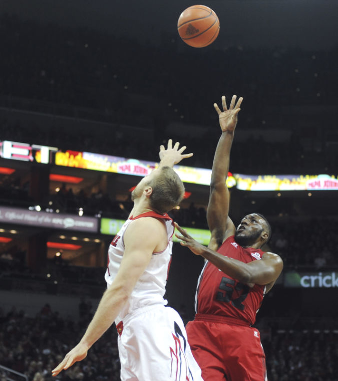 Junior guard T.J. Price shoots over Louisville senior guard Tim Henderson during their game Saturday at KFC Yum! Center in Louisville, Ky. WKU lost 79-63.