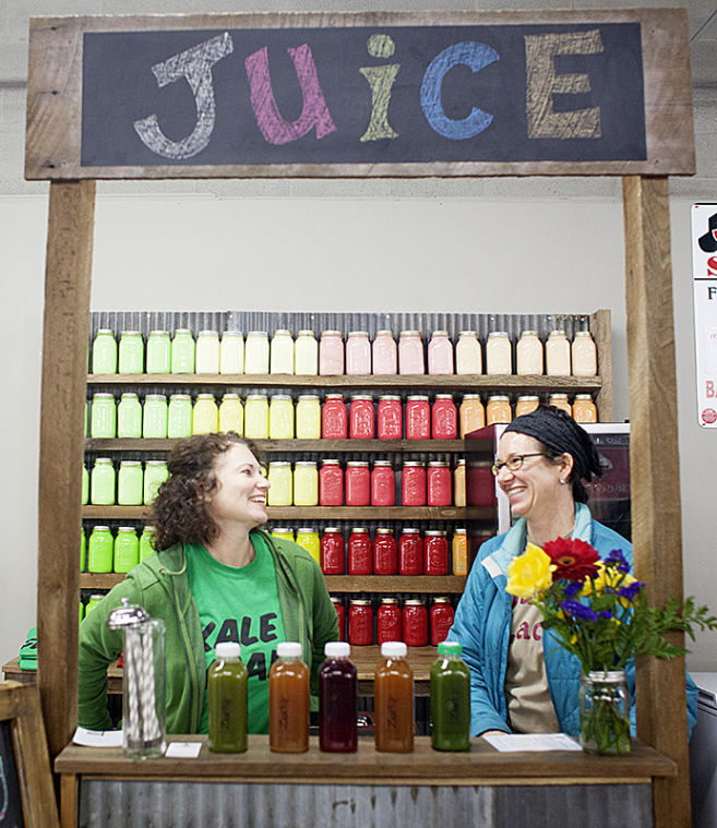 WKU alumni Natalie Boddeker and Tonia Johns laugh behind the counter of their stand at Community Farmer's Market. Boddeker and Johns met while working at Barnes and Noble in Bowling Green and decided to start Zest!, a juice business, after realizing that they could make a profit off of their shared interest in juice cleanses.