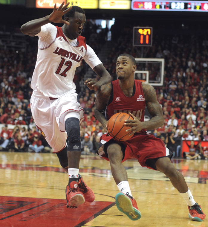 Junior guard Trency Jackson drives past Louisville freshman forward Mangok Mathiang during their game Saturday at the KFC Yum! Center in Louisville, Ky. WKU would lose the game 63-79.