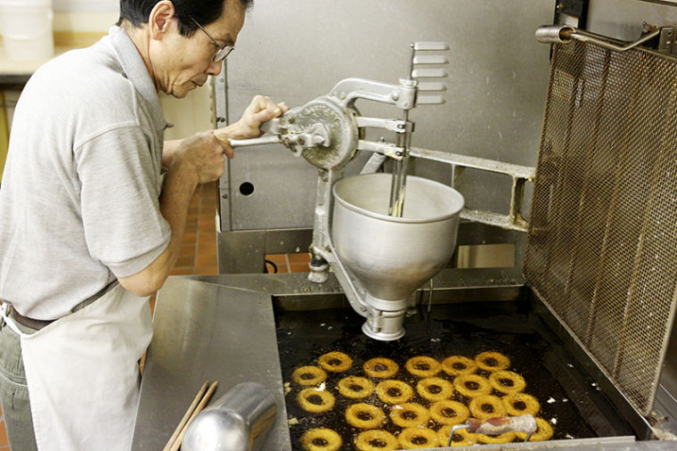 Eak+Taing%2C+56%2C+makes+donuts+in+the+kitchen+of+Great+American+Donuts.+Taing+moved+to+the+United+States+from+Cambodia+when+he+was+24.+Taing+said+he+has+been+making+donuts+for+about+20+years.+He+said+they+still+make+donuts+the+old+fashion+way.