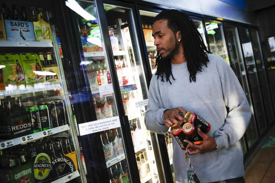 Clarksville, Tenn., junior Aarion Hinds buys a six-pack of Redd's Apple Ale from Shenanigans Wines and Spirits in Bowling Green on Sunday, Jan. 26, 2014.