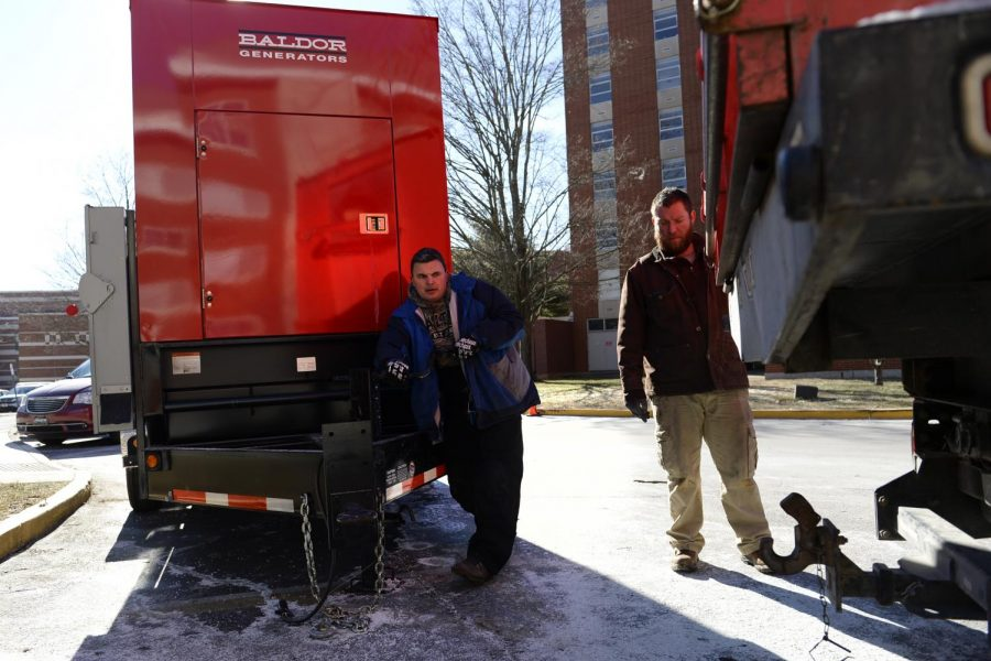 Adam Garret and Travis Kugler, both of Bowling Green, Ky., guide a truck as they hook up a generator in front of Southwest Hall Thursday afternoon. A bursted water main in Northeast Hall caused a short that knocked out power in three dorm rooms.