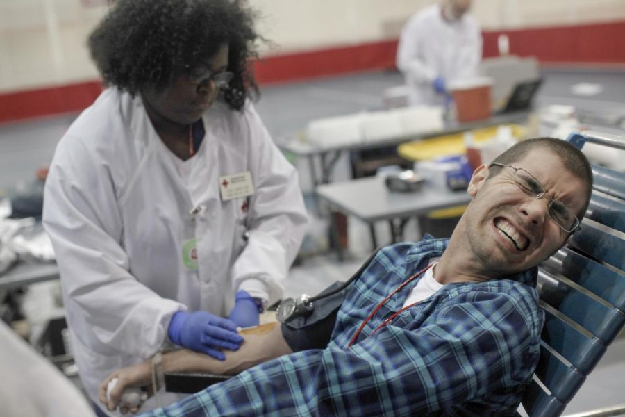 Sophomore+Michael+Karimian+of+Louisville+grimaces+as+a+Red+Cross+employee+puts+a+needle+in+his+arm+at+a+blood+drive+Thursday+at+the+Preston+Center+sponsored+by+Campus+Ministries+and+the+American+Red+Cross.+Karimian+said+that+the+needle+going+in+is+the+only+part+that+bothers+him+and+that+the+rest+is+fine.+%28Austin+Anthony%2FHERALD%29