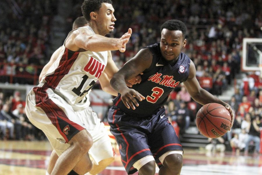 Ole Miss point guard Derrick Millinghaus attempts to push past Topper freshman point guard Brandon Harris during their match at Diddle Arena on Dec. 30, 2013. The Ole Miss Rebel Black Bears defeated the Toppers 79-74. (Rae Emary/HERALD)