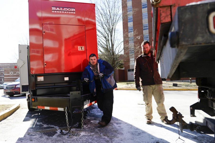 Adam Garret and Travis Kugler, both of Bowling Green, guide a truck as they install a generator in front of Southwest Hall. A busted water main in Northeast Hall caused a short that knocked out power in Bates-Runner, Northeast and Southwest Halls. (Ian Maule/HERALD)