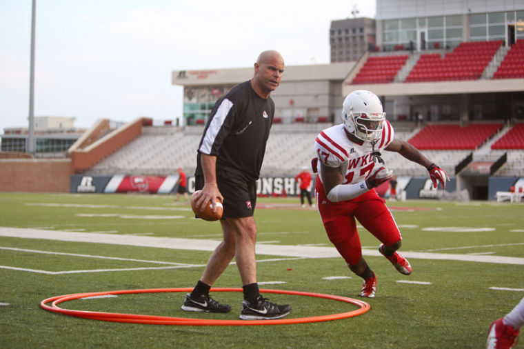 Hilltopper Defensive Coordinator Nick Holt (left) yells to linebacker Daqual Randall, No. 17, to catch a relay partner in a running exercise during practice on Wednesday at Smith Stadium.