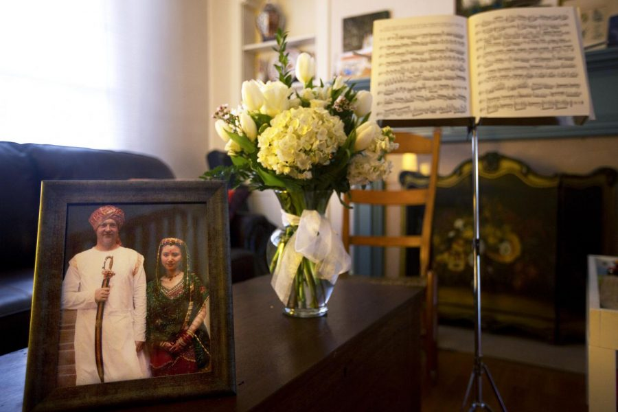 Mei Du's and her late husband, Lindsey Powell's, wedding photograph along with flowers from a student and Powell's music stand at their home on Feb. 21. (Demetrius Freeman/HERALD)