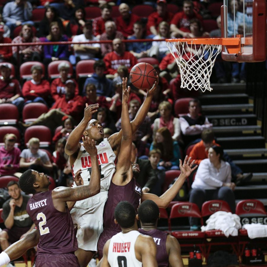 WKU's junior guard Aaron Adeoye (11) goes for a rebound over ULM's forward Jayon James (1) during the first half of WKU's 72-63 victory over the University of Louisiana-Monroe Saturday, Feb. 22, 2014 at Diddle Arena in Bowling Green, Ky. (Mike Clark/HERALD)