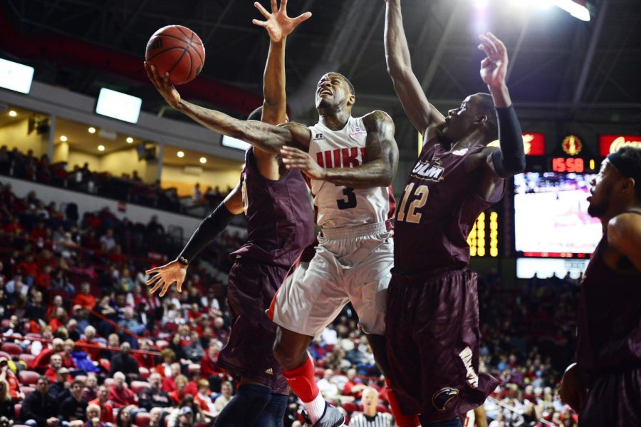 Junior guard Trency Jackson drives past Louisana-Monroe junior center Marvin Williams and junior forward Tylor Ongwae during the first half of their game at Diddle Arena on Thursday, Feb 22. The Toppers defeated the Warhawks 72-63. (Ian Maule/HERALD)