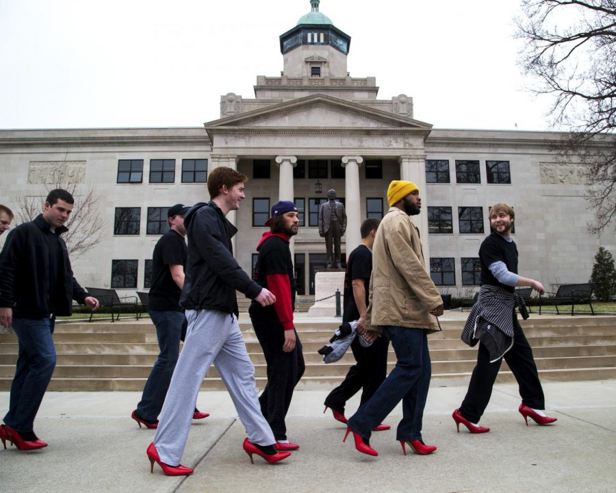 Participants in Walk a Mile in Her Shoes strut past Cherry Hall on Tuesday to raise awareness about sexual assault. Proceeds from the event go to Hope Harbor, which provides counseling and support to victims of sexual assault. (Mike Clark/HERALD)