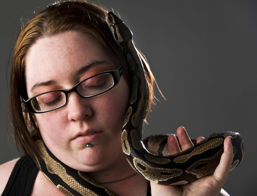 Tiffany Quiles poses for a portrait with her snake, King Bubba Camou. Quiles received the snake on her 16th birthday. Since then, she has acquired multiple reptiles. (Kreable Young/HERALD)