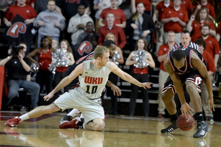Senior guard Caden Dickerson dives for a lose ball against Arkansas State senior guard Ed Townsel and sophomore forward Kelvin Downs during the second half of the Tops 82-77 double overtime win.