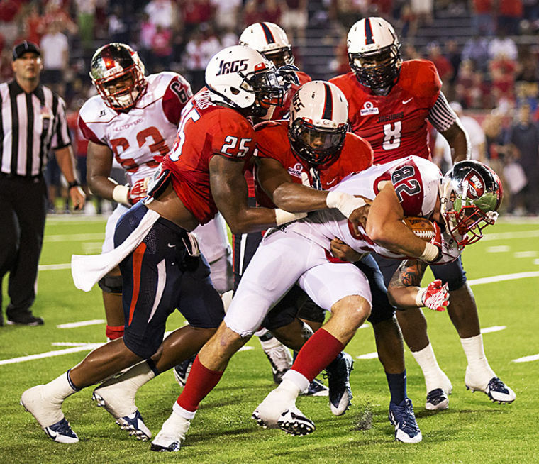 Tightend Tyler Higbee (82) is tackled by offensive lineback Clifton Crews (25) and offensive lineback Maleki Harris (6) during the second half of WKU's game against Southern Alabama Sept. 14, 2013 at Ladd - Pebbles Stadium in Mobile Ala.