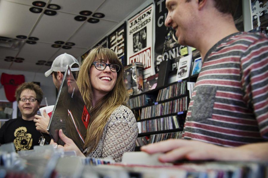 WKU folk studies graduate student Kaitlyn Berle from Ohio finds a record and shows it to fellow graduate student Josh Chrysler during record store day at Mellow Matt's on Saturday. (Brian Powers/HERALD)