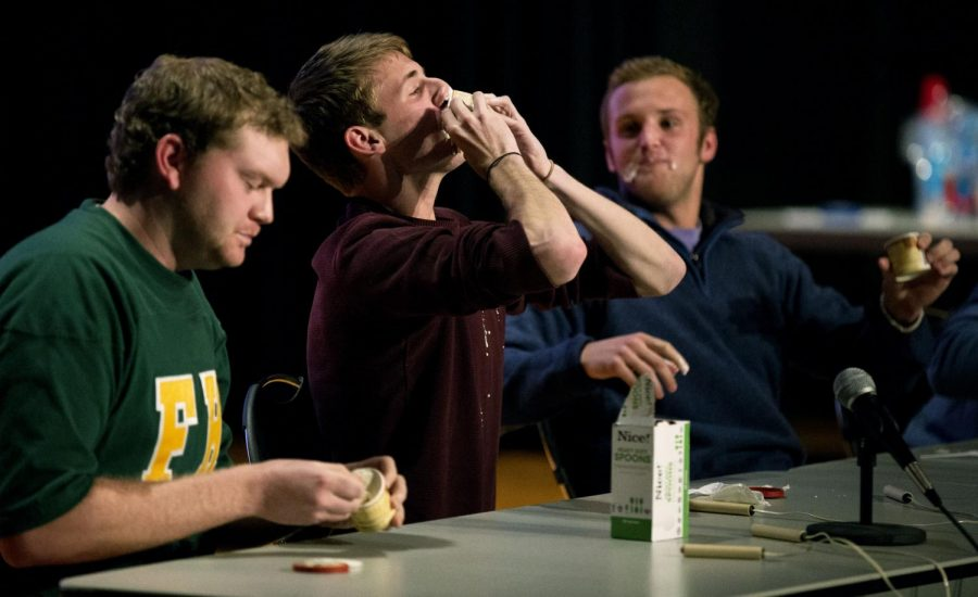 Morganfield senior Coleman West of Farmhouse fraternity (left), La Grange sophomore Colton Hounshell of Phi Gamma Delta fraternity (center), and Lexington freshman Marshal Aiken of Sigma Alpha Epsilon fraternity compete in an ice cream eating challenge during Greek Feud Tuesday at the Downing Student Union auditorium. (Mike Clark/HERALD)