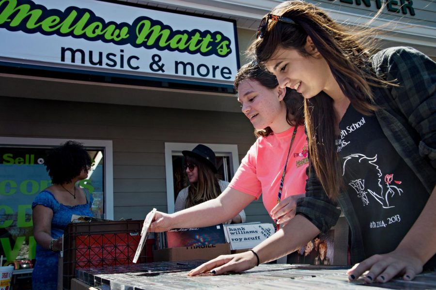 Alex Kary, front, and Carrie Mahagan, back, both 17 of Bowling Green, sort through boxes of CDs and records during record store day at Mellow Matt's on Saturday. (Brian Powers/HERALD)