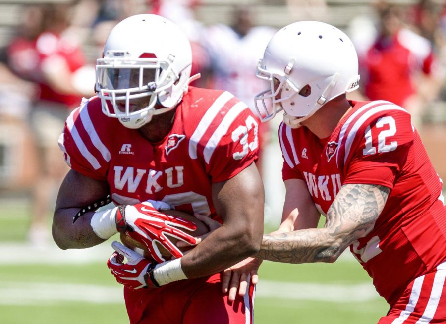 Junior running back Leon Allen (33) takes a handoff from redshirt senior quarterback Brandon Doughty (12) during the Red and White Spring Game Saturday, April 19, 2014, at Houchens Industries - L.T. Smith Stadium in Bowling Green, Ky. (Mike Clark/HERALD)