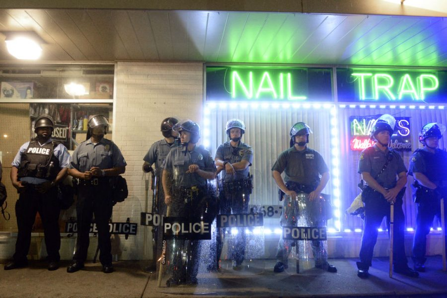 August+16%2C+2014%2C+Ferguson%2C+Mo+USA_+%7C+Police+stands+with+riot+gear+in+front+of+shops+to+protect+from+looting+and+look+on+as+protesters+march+peacefully+on+W.+Florissant+St.+during+the+first+night+of+curfew+declared+by+Gov.+Jay+Nixon+on+Saturday+Aug.+16%2C+2014+in+Ferguson%2C+Mo.+Jeff+Brown%2FHERALD