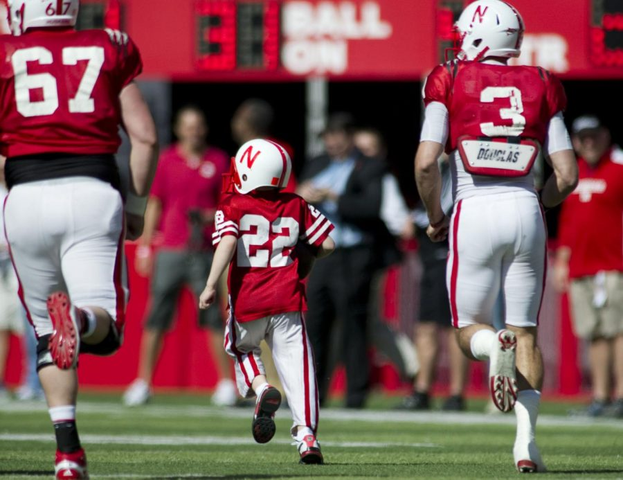 Nebraska's Taylor Martinez (3) and Scott Criss (67) guide Jack Hoffman down the field on his touchdown run during the second half of the 2013 Red-White Spring Game.
