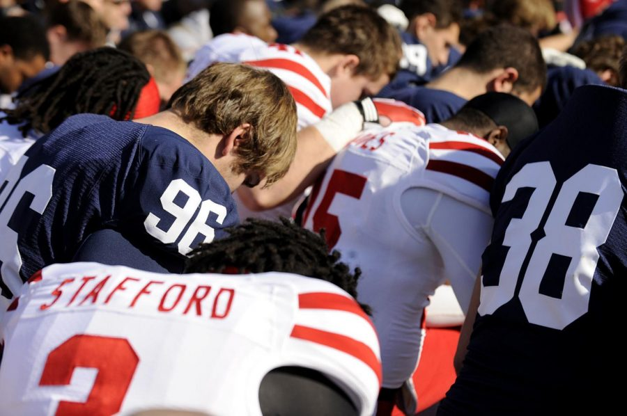 STATE COLLEGE, PA. - 11/12/2011 - Penn State tackle Cody Castor (96) and linebacker Ben Kline (38) kneel in prayer with Huskers Brion Carnes (15) and Daimion Stafford (3) during a pre-game prayer delivered by Nebraska running backs coach Ron Brown at Beaver Stadium on Saturday, November 12, 2011. (FRANCIS GARDLER / Lincoln Journal Star)