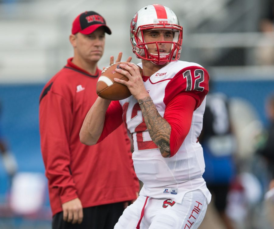 Head Coach Jeff Brohm watches quarterback Brandon Doughty in warmups before the WKU vs Middle Tennessee State University game on Sept. 13, 2014. Nick Wagner/HERALD