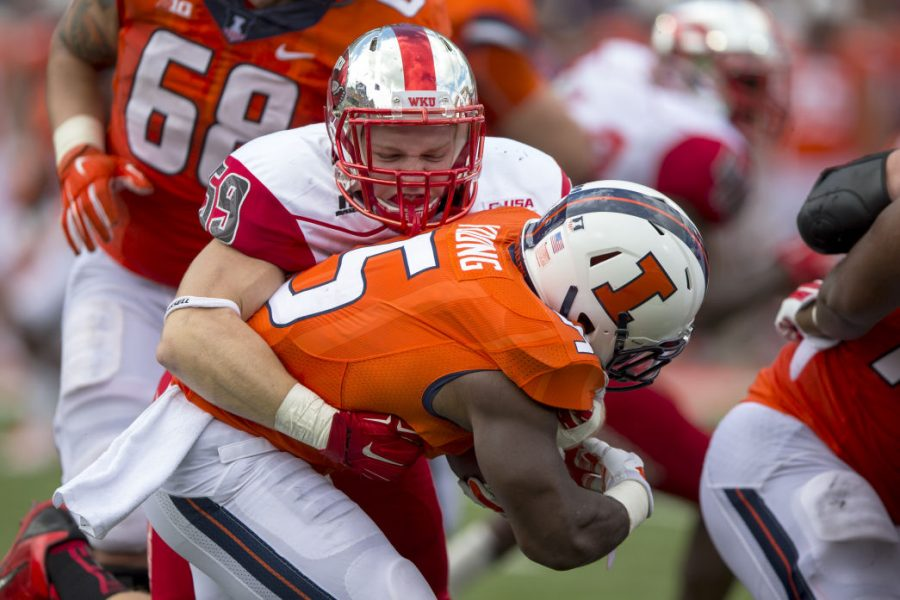 Redshirt defensive lineman Tanner Reeves (59) tackles the Illini's running back Donovonn Young (5) during the second half of WKU's 34-42 loss against the University of Illinois Saturday, Sept. 6, 2014, at Memorial Stadium in Champaign, Ill. Mike Clark/HERALD