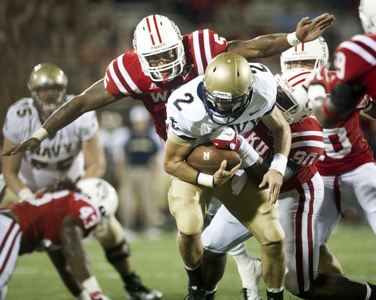 Defensive lineman Jared Clendenin helps Bo Adebayo bring down Navy quarterback Kriss Proctor for a sack during the third quarter of WKU's 40-14 loss to Navy at Smith Stadium.