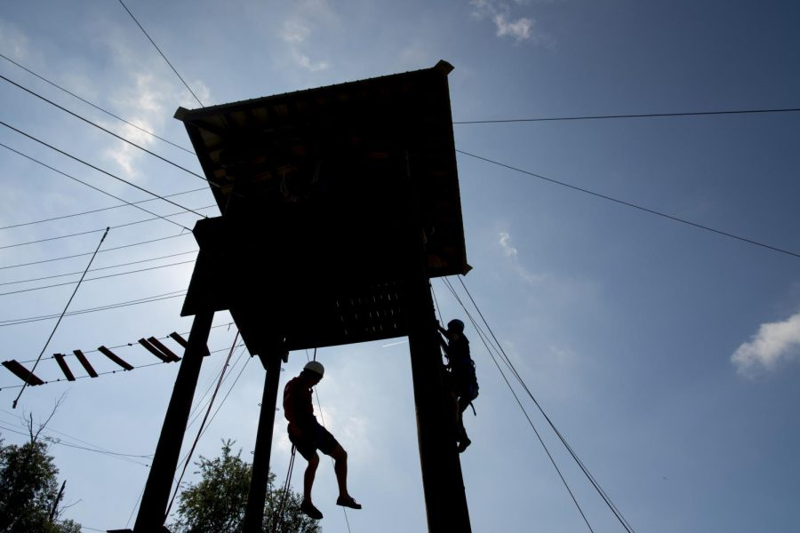Frankfort senior AJ Snipes, 23, repels down the open face of the WKU Challenge Course as Hebron senior Thomas Kinman, 21, ascends the rock wall. Students in the Recreation Administration major have the option to complete REC 439: Challenge Course Facilitation, for a concentration in Outdoor Recreation. William Kolb/HERALD