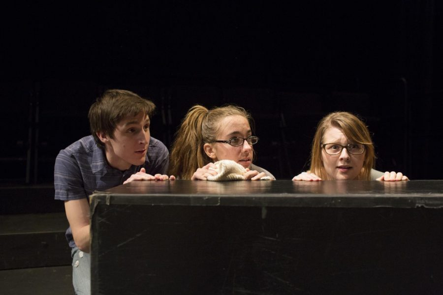 WKU students Gabriel Pless, Heather Moore and Asya Hildenbrand (left to right) peer from behind a wooden box during rehearsal of