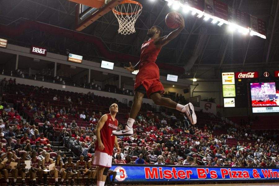 Redshirt senior Trency Jackson leaps for a dunk after a pass from senior guard Kevin Kaspar during the slam dunk contest at Hilltopper Hysteria on Oct. 18 at Diddle Arena. Jackson, last year's slam dunk contest champion, lost to his teammate Ayinde Spreewell. Brandon Carter/HERALD