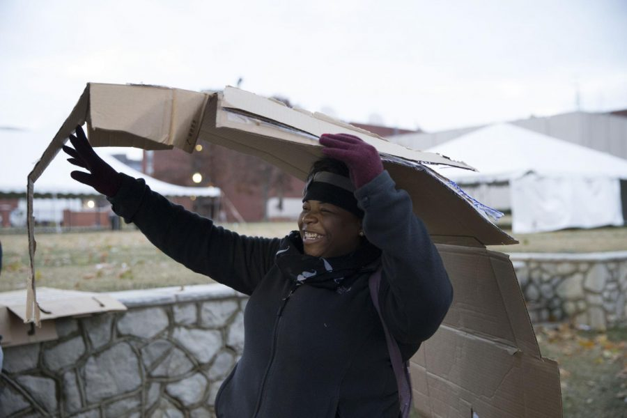 Clarksville, Tennessee sophomore Malika Pitt carries a cardboard box that her group used as building material at the homelessness awareness event, Shantytown, during Hunger & Homelessness Awareness Week Monday on South Lawn. Student teams were given scenarios of homelessness and then constructed shelters meeting requirements of the scenario. Mike Clark/HERALD