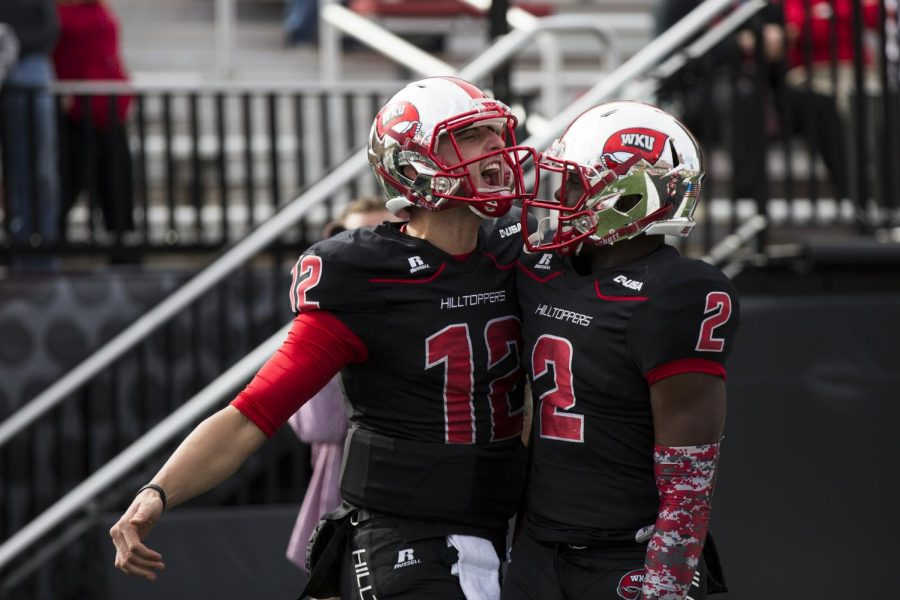 Redshirt senior quarterback Brandon Doughty (12) celebrates with sophomore wide receiver Taywan Taylor (2) after rushing for a 15-yard touchdown during the first half of the WKU-Army game on Nov. 15. The Hiltoppers led the Black Knights 24-10 at the half. Brandon Carter/HERALD