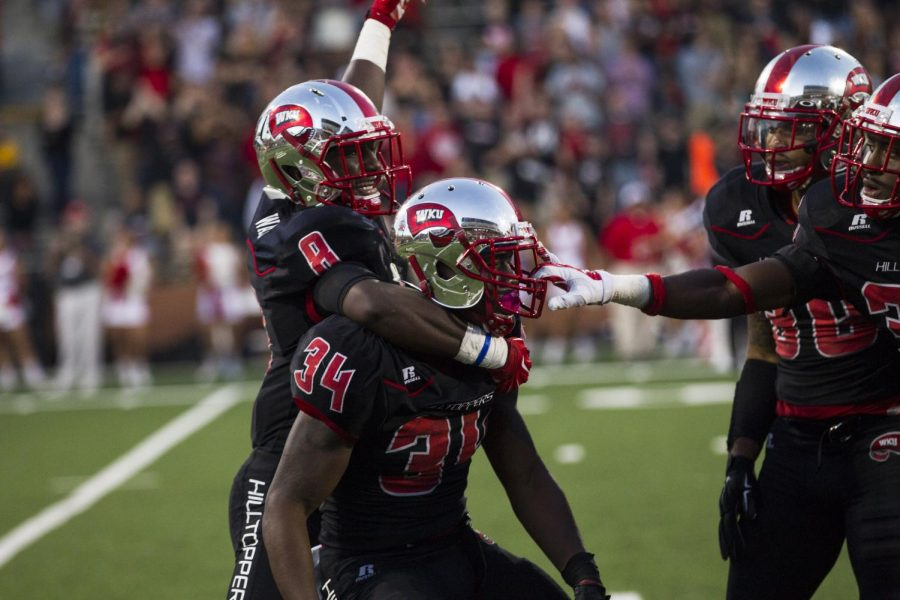 Sophomore linebacker Drew Davis (34) is mobbed by teammates, including sophomore defensive back Marcus Ward (8), after making a huge hit on an Old Dominion kick returner during the second half of WKU's Oct. 25 game against the Monarchs. Davis had two tackles as the Hilltoppers defeated ODU 66-51.Brandon Carter/HERALD