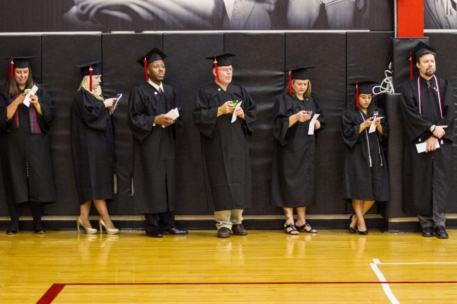 Members of WKUs class of 2014 look at their phones as they wait for the beginning of WKUs commencement ceremony for the Godon Ford College of Business, University College and College of Health and Human Services, Saturday, Dec. 13, 2014, at E.A. Diddle Arena in Bowling Green, Ky.