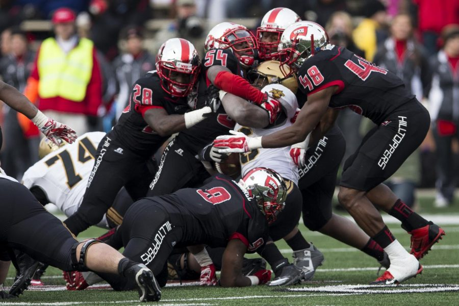 A host of WKU defenders tackle Army running back Larry Dixon during the second half of WKU's Nov. 15 game against Army. The Hilltoppers' defense held the Black Knights to an average of 5.3 yards per carry, leading WKU to a 52-24 victory. Brandon Carter/HERALD