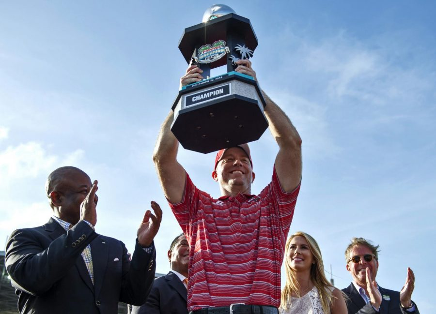 WKU head coach Jeff Brohm hoists the championship trophy above his head following the Hilltoppers 49-48 win over Central Michigan in the Popeyes Bahamas Bowl game in Nassau on Wednesday, Dec. 24, 2014.